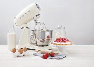 Robot sur socle smeg creme avec dessert sur la table